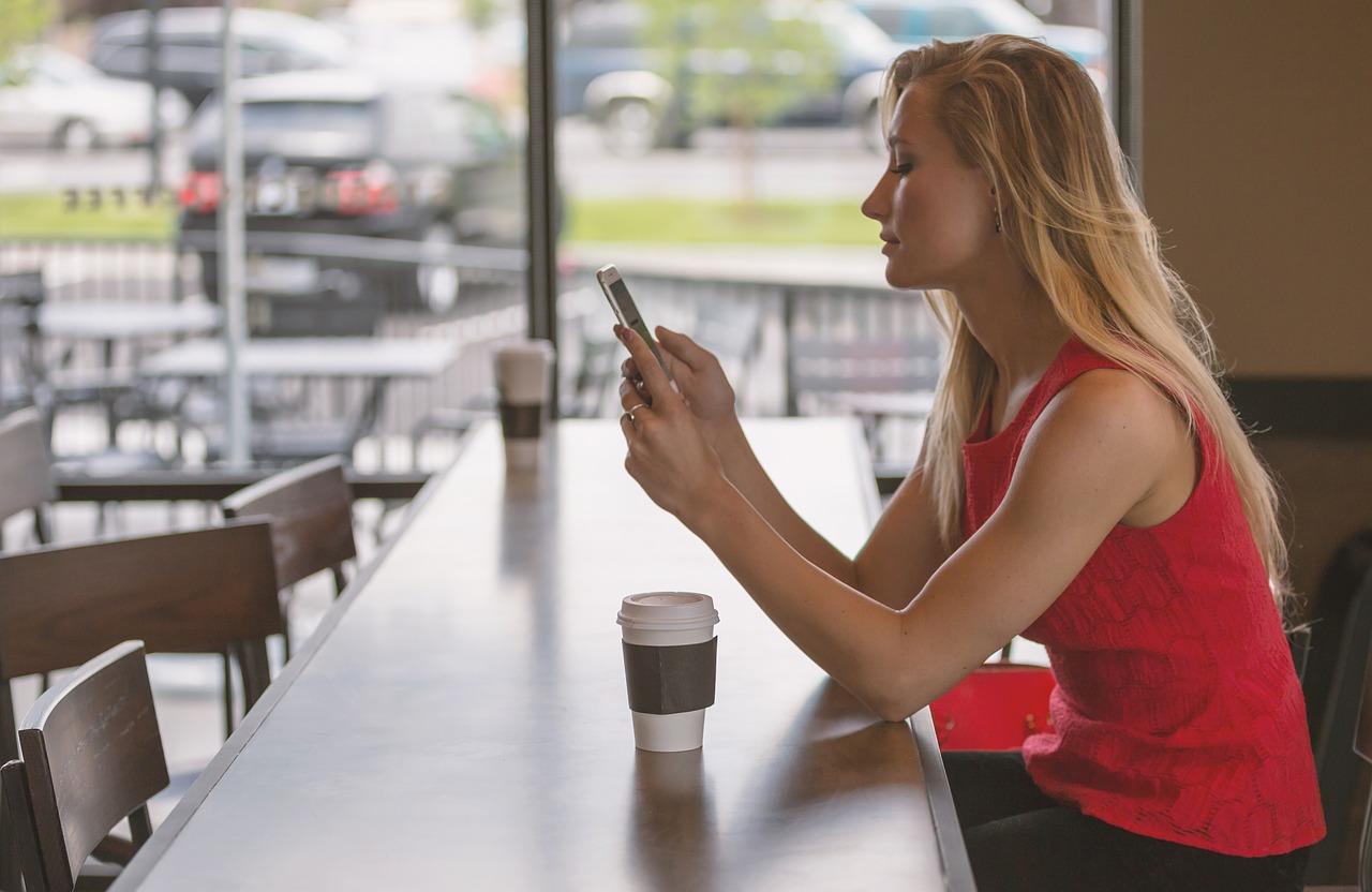 Frau sitzt im Kaffee und schaut auf ihr Smartphone