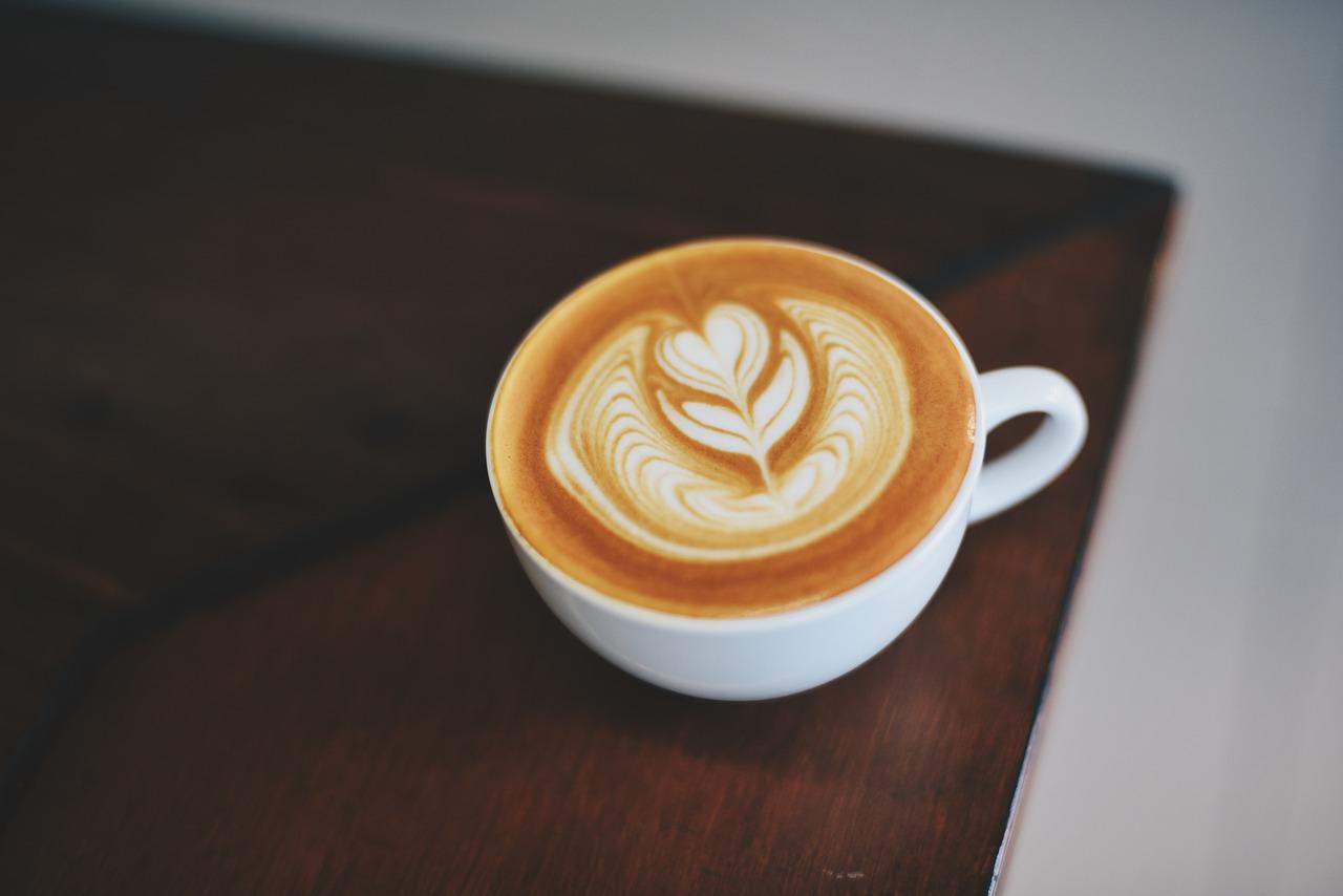 Kaffee steht in einer weißen Tasse auf einem dunkel Braunen Tisch. Der Milchschaum sieht aus wie eine Blume.