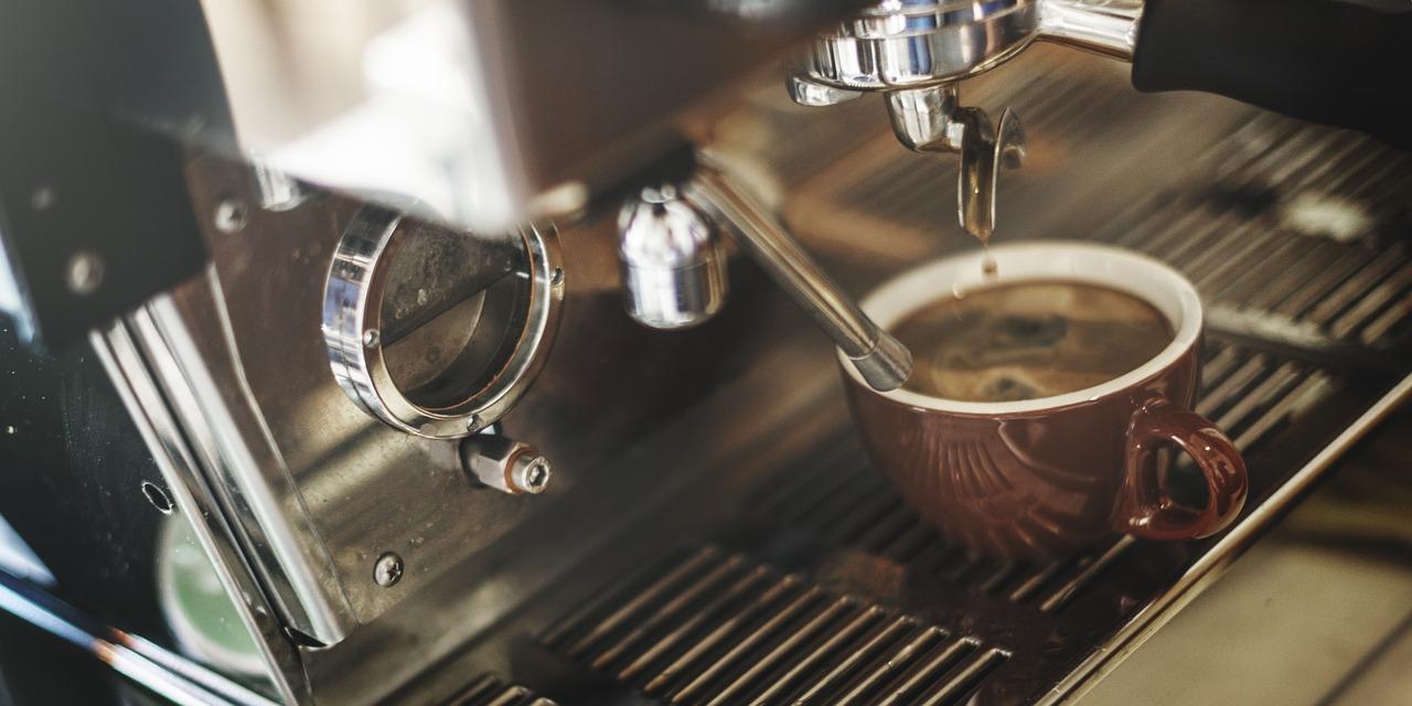 Auf einer Kaffeemaschine steht eine Tasse mit Kaffee in einer dunklen Tasse.