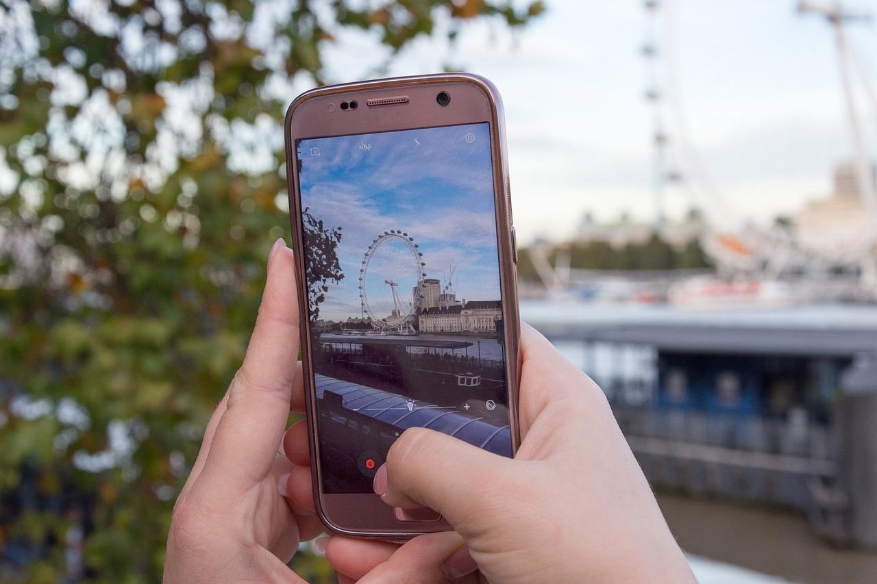 Jemand hält ein Smartphone in der Hand und Fotografiert ein Riesenrad.
