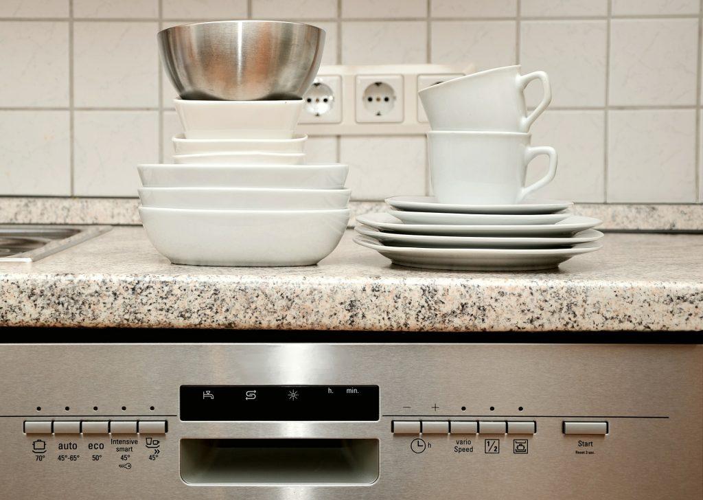 Tassen und Teller stehen auf einer Spülmaschine.