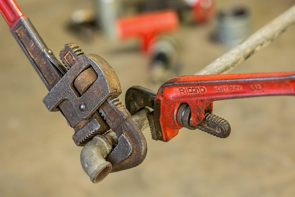 Zwei Rohrzangen bearbeiten ein Rohr aus Metall